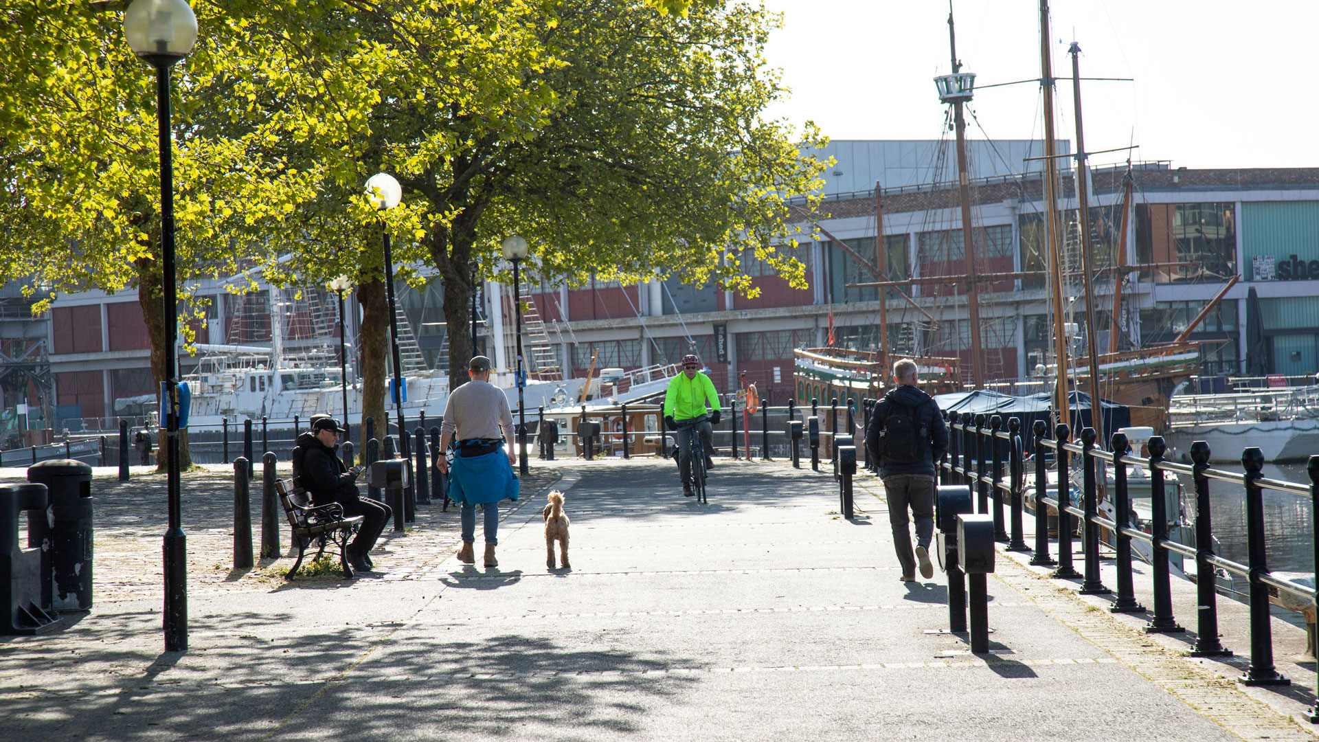 People walking and cycling alongside Bristol floating harbour